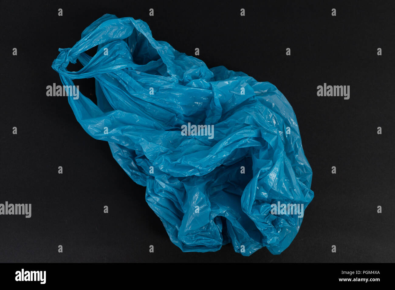 Old used crumpled blue shopping plastic or garbage bag as single use waste environment pollution concept isolated on black background - Stock Image
