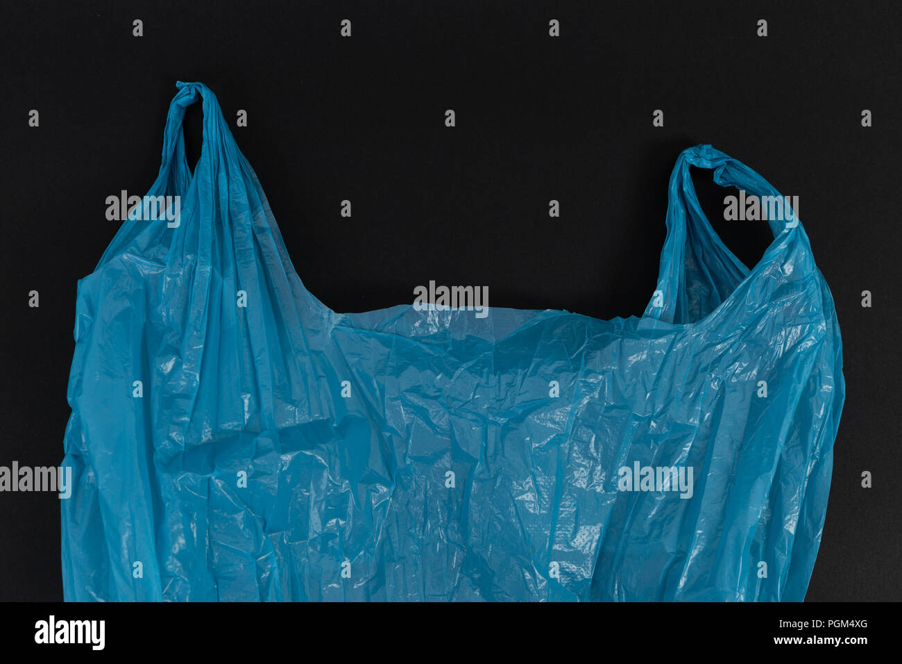 Used crumpled single use blue plastic bag with handles as waste pollution environment ecology concept isolated on black background Stock Photo