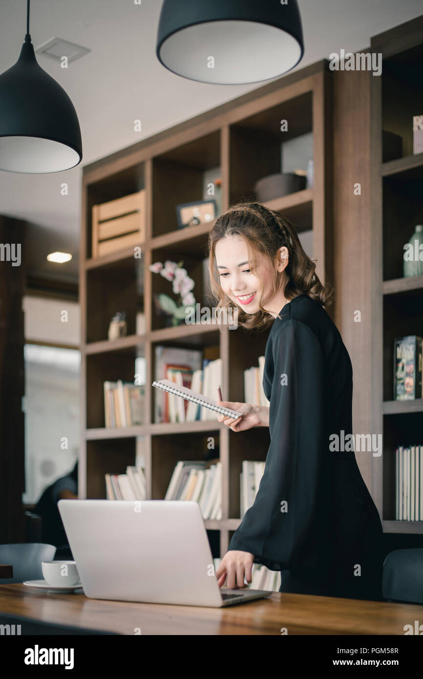 Confident happiness young woman working on laptop or notebook in her office. Beautiful Freelancer Woman working online at her home. Beauty Asian busin - Stock Image