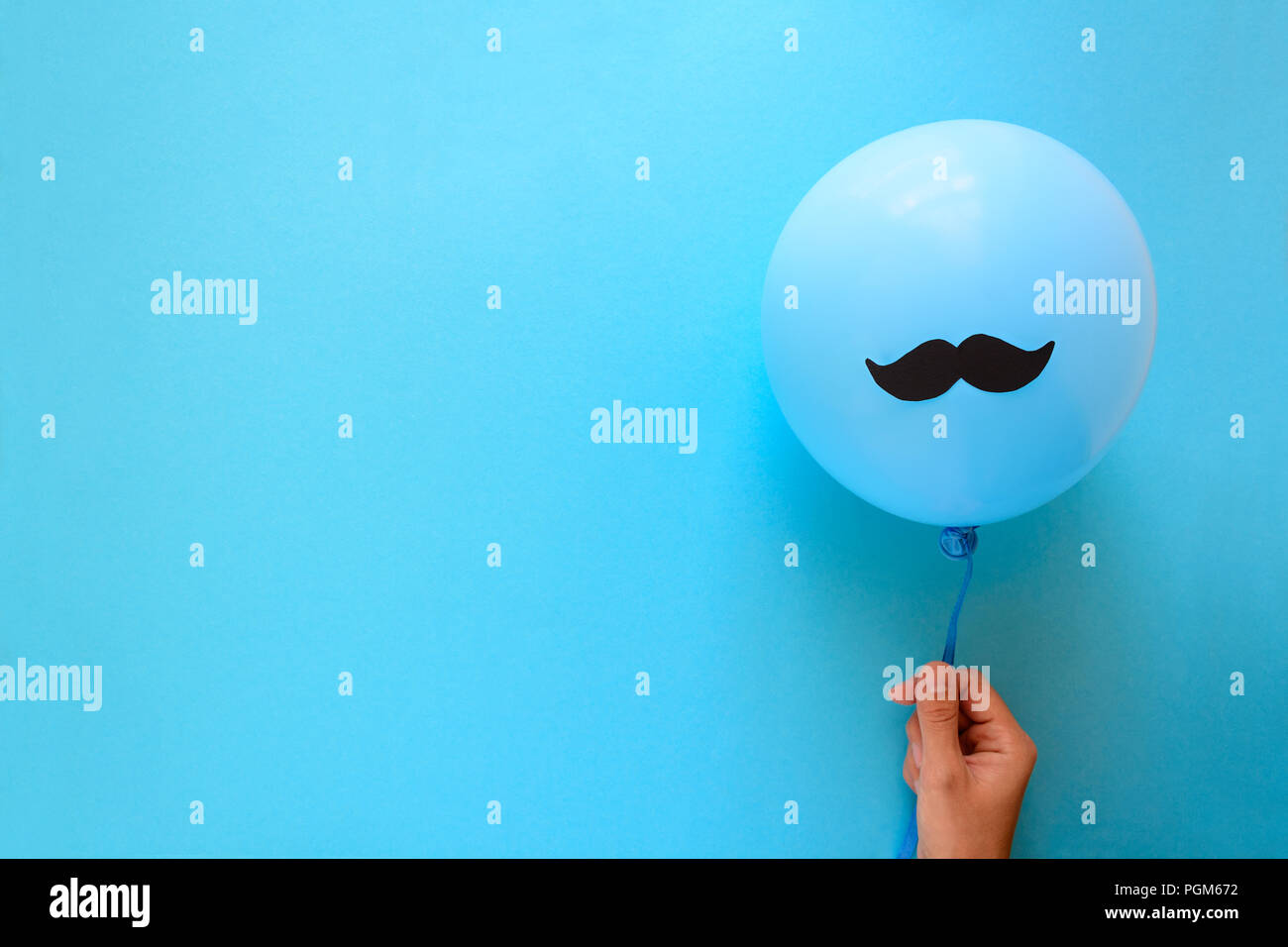 Hand holding blue balloon with a paper mustache on blue paper background. Cut out style. Movember - Stock Image
