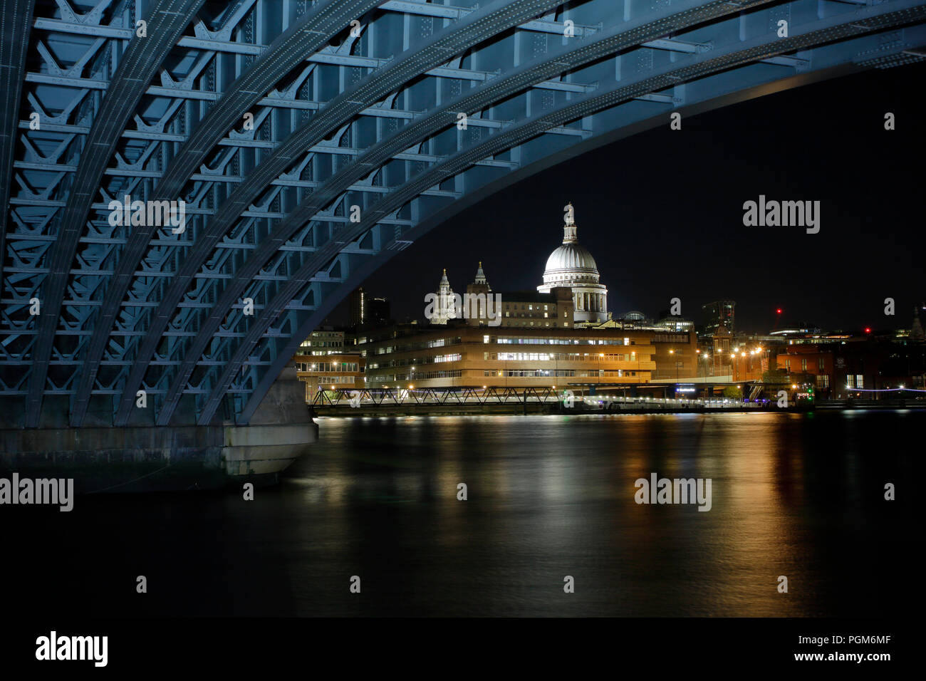 Saint Pauls Cathedral from under Blackfriars Bridge at night, bridge structure has been light painted with a daylight balanced lamp. - Stock Image