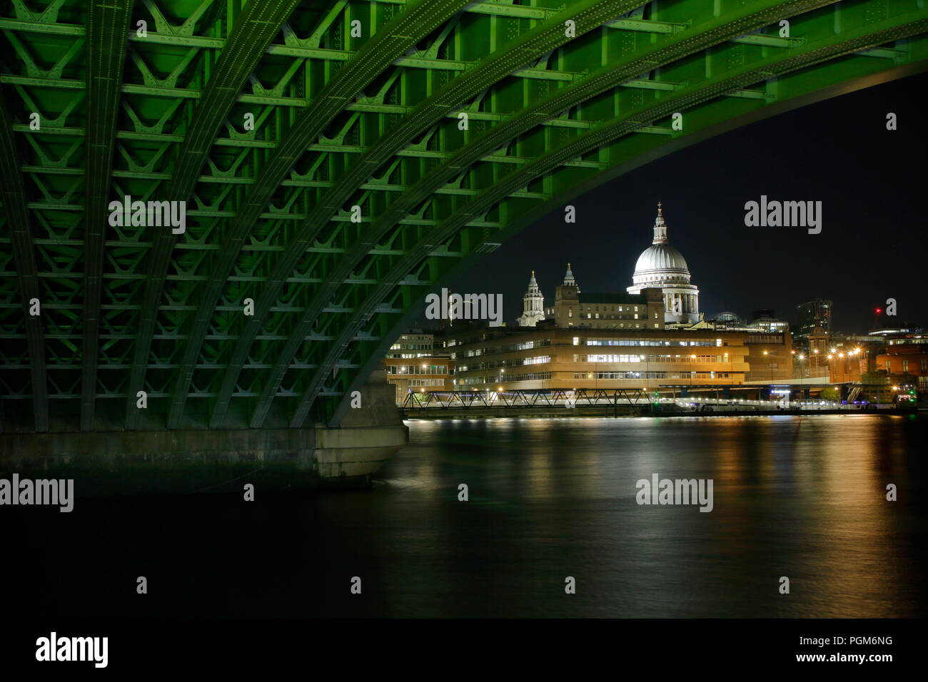 Saint Pauls Cathedral from under Blackfriars Bridge at night, bridge structure has been light painted with a daylight balanced lamp. Stock Photo
