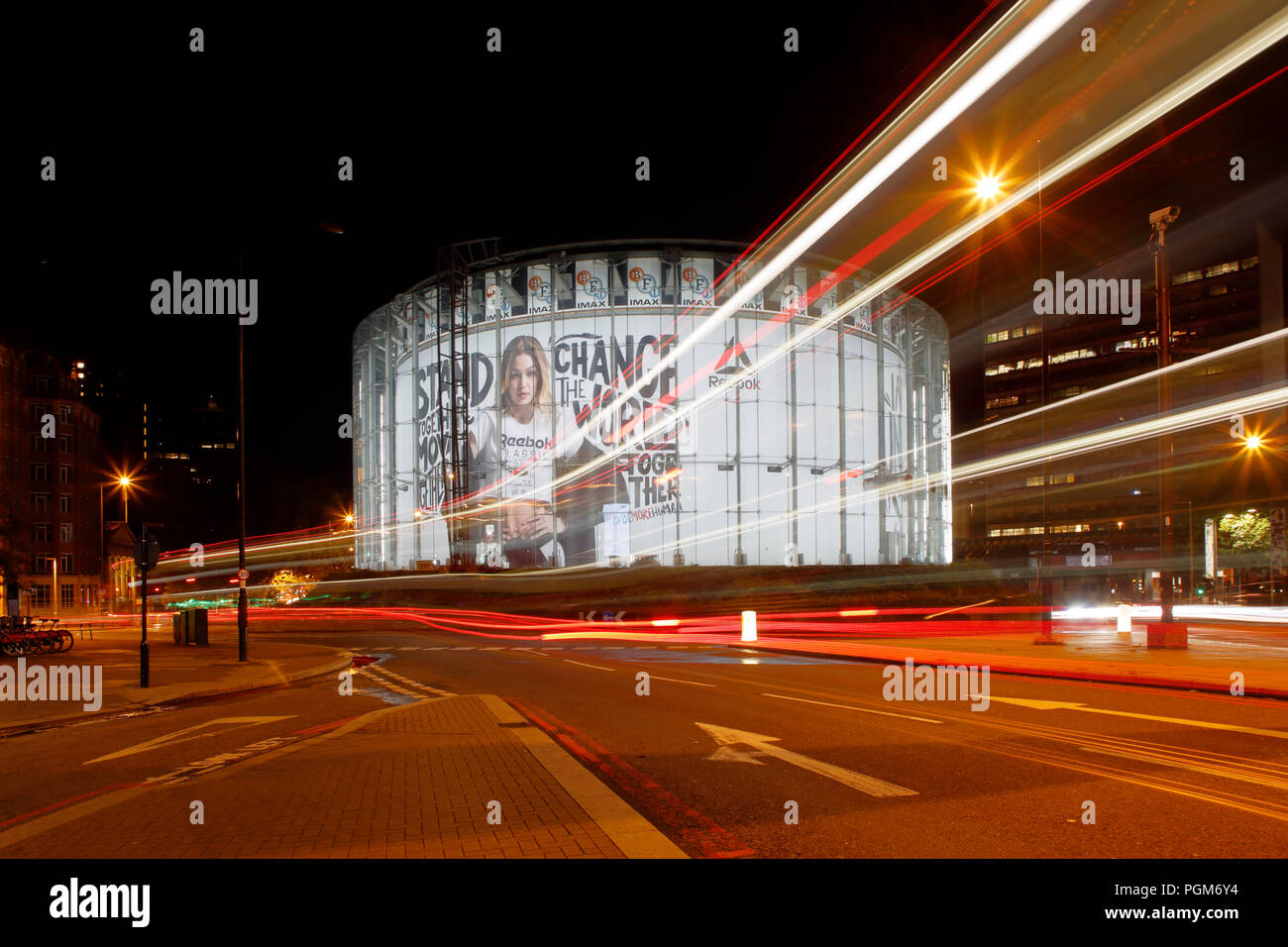 London BFI IMAX cinema at Waterloo, photographed at night, long exposure to include light trails left by passing traffic. - Stock Image