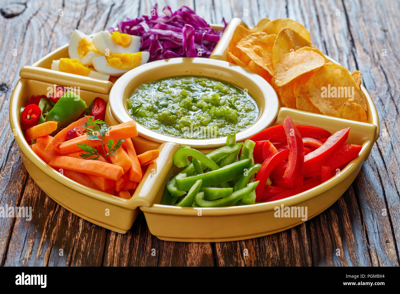 green salsa verde and mexican set of chopped fresh vegetables, hard boiled eggs  and chips in bowls on old rustic wooden board. ingredients for tacos, Stock Photo