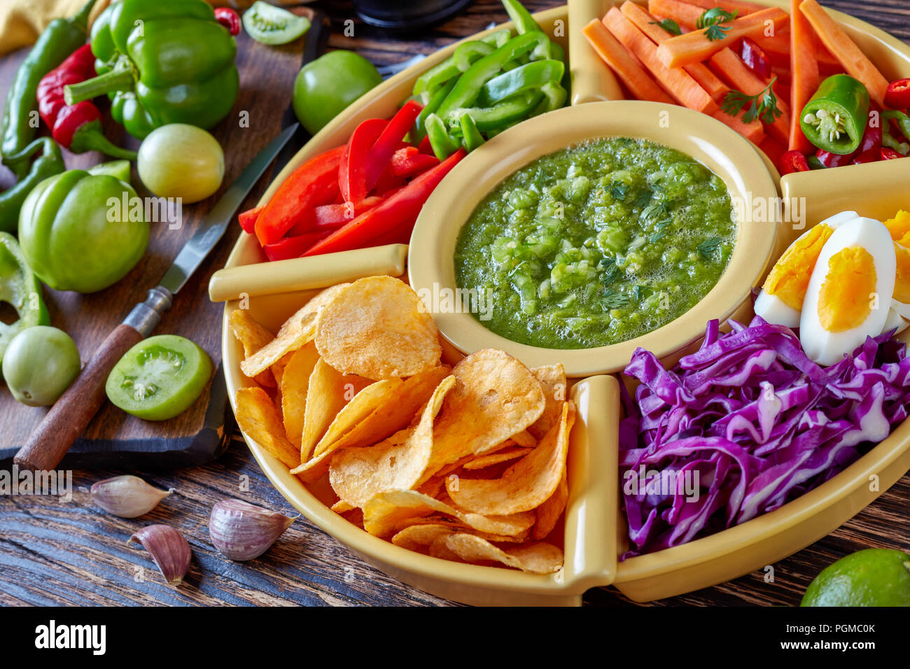 green salsa verde and mexican set of chopped fresh vegetables, hard boiled eggs and chips in bowls on old rustic wooden board with ingredients, horizo Stock Photo