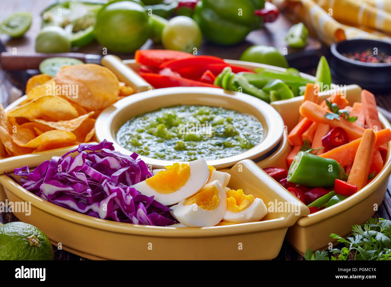 green salsa verde and mexican set for tacos consist of chopped fresh vegetables, hard boiled eggs and chips in bowls on old rustic wooden table with i Stock Photo