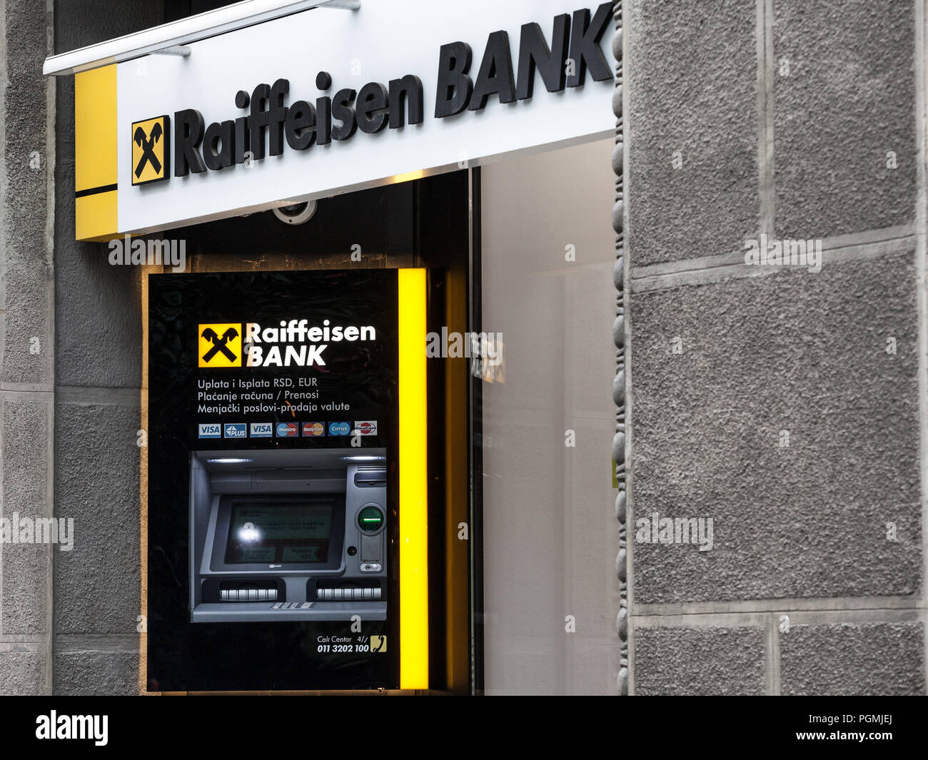BELGRADE, SERBIA - AUGUST 26 , 2018: Raiffeisen logo on their main bank in Belgrade, with their ATm in background. Raiffeisen is an Austrian bank, mas - Stock Image