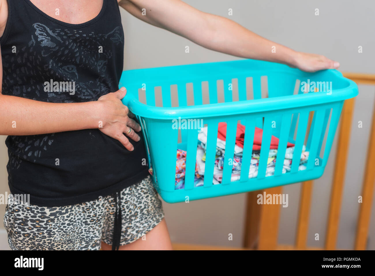Young woman doing housework holding a basket with laundry - Stock Image