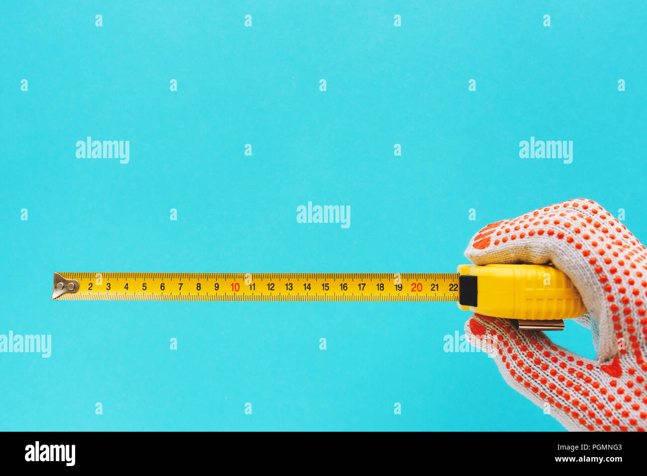 Handyman measuring size with tape meter, hand with tool isolated on blue background - Stock Image