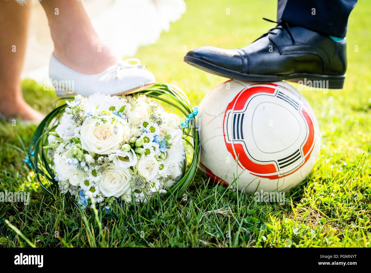 Bride and groom put their feet on the football - Stock Image