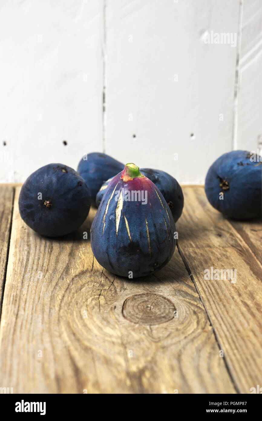 Fresh purple figs on wooden surface with light background, space for copy - Stock Image