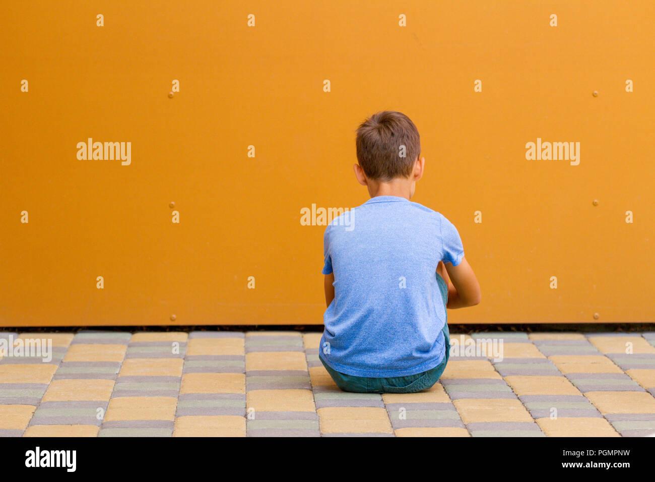 Sad alone boy sitting near colorful wall outdoors. - Stock Image
