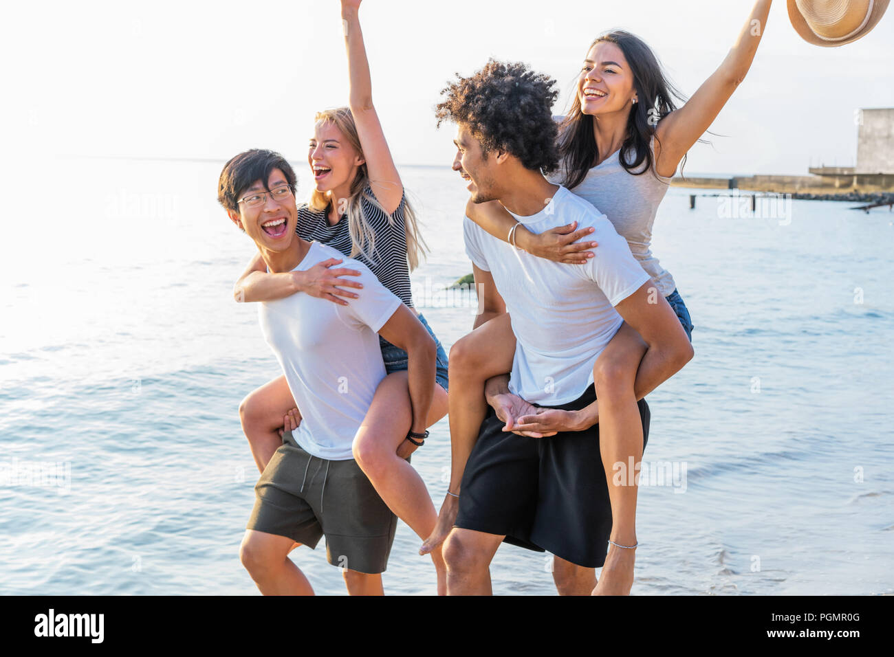 Group of friends walking along the beach, with men giving piggyback ride to girlfriends. Happy young friends enjoying a day at beach - Stock Image