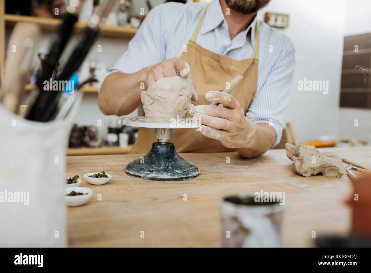 Bearded ceramist having creative ideas while using ceramics jigger - Stock Image