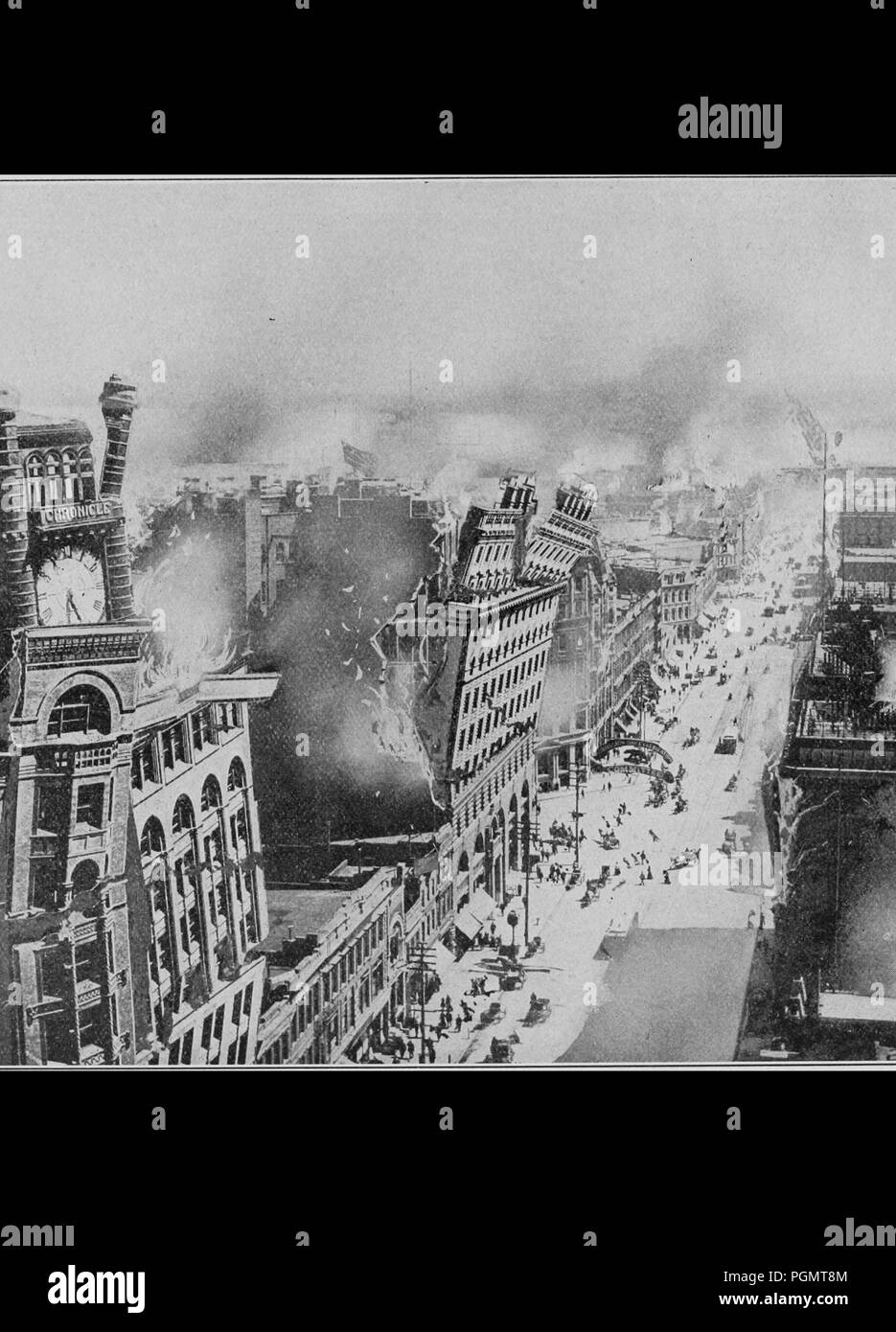 Black and white photograph showing a city street with people, cars, and horse-drawn wagons on the road below, while multi-story buildings tear apart as flames leap from their roofs following a series of aftershocks during SanFrancisco's 1906 earthquake, 1906. Courtesy Internet Archive. () - Stock Image