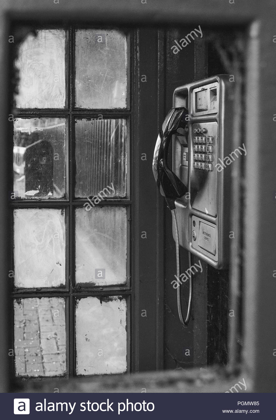 Broken phone box on a London street. This hasn't been used in years, though the phone itself seems to have survived the test of time. - Stock Image