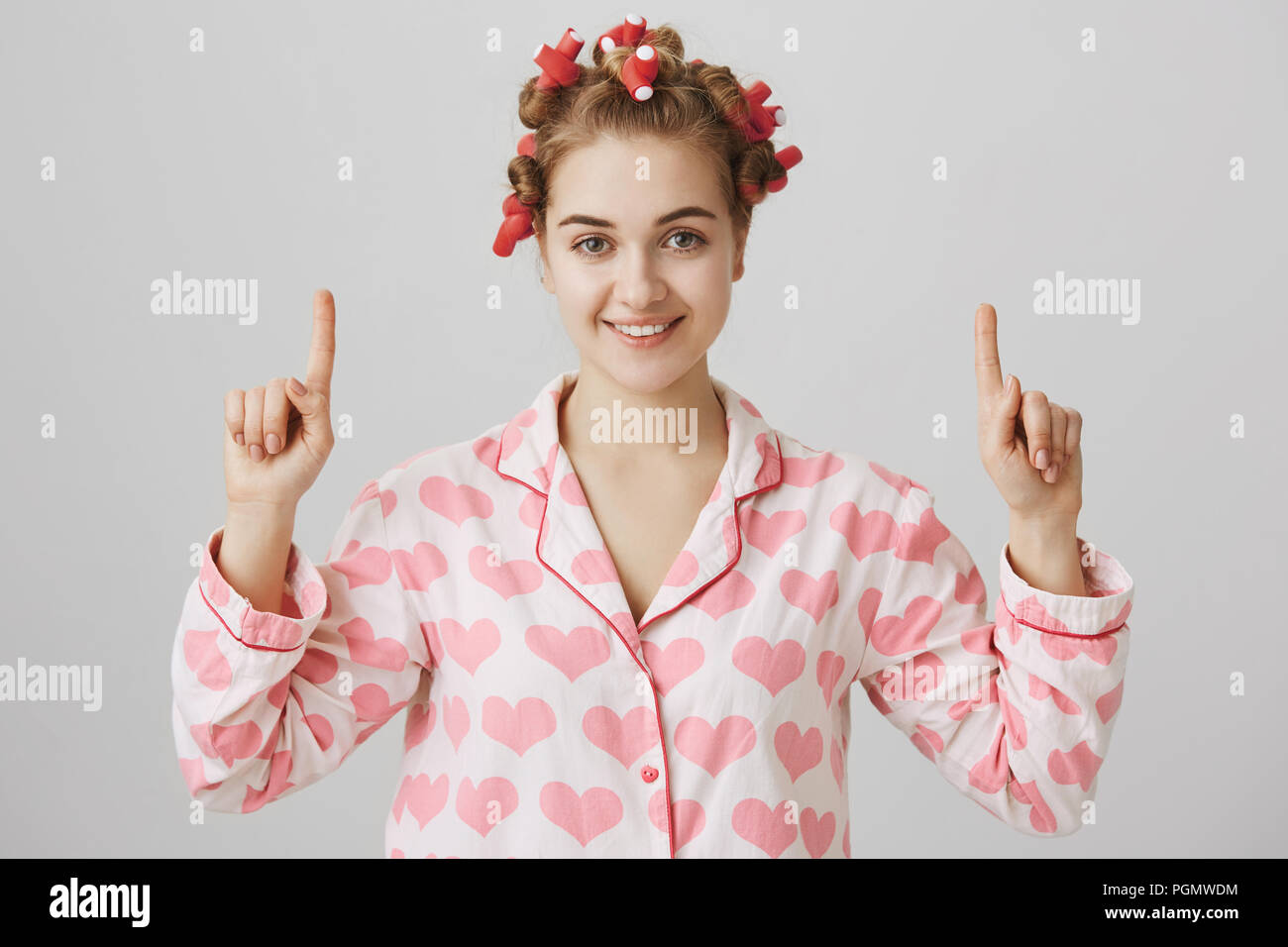 Cute and feminine european girl in hair-curlers and nightwear, pointing up with index fingers, smiling and glancing at camera over gray background. Woman glad she learnt how to apply curlers Stock Photo