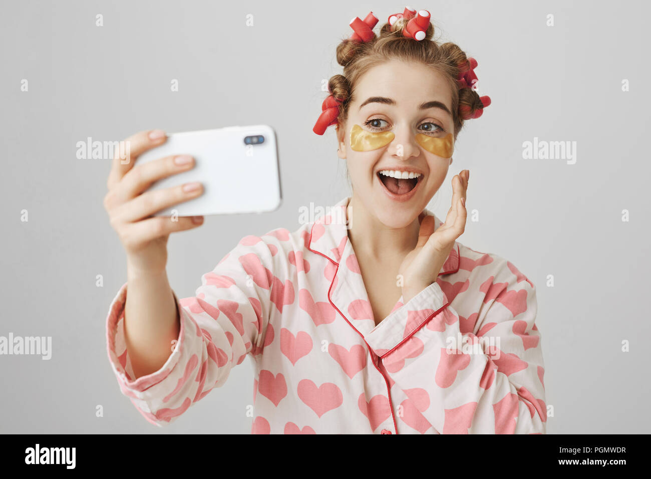 Playful good-looking girl at home making beauty procedures, wearing hair-curlers, nightwear and eye patch mask, smiling while taking selfie or recording video via smartphone, over gray background. - Stock Image