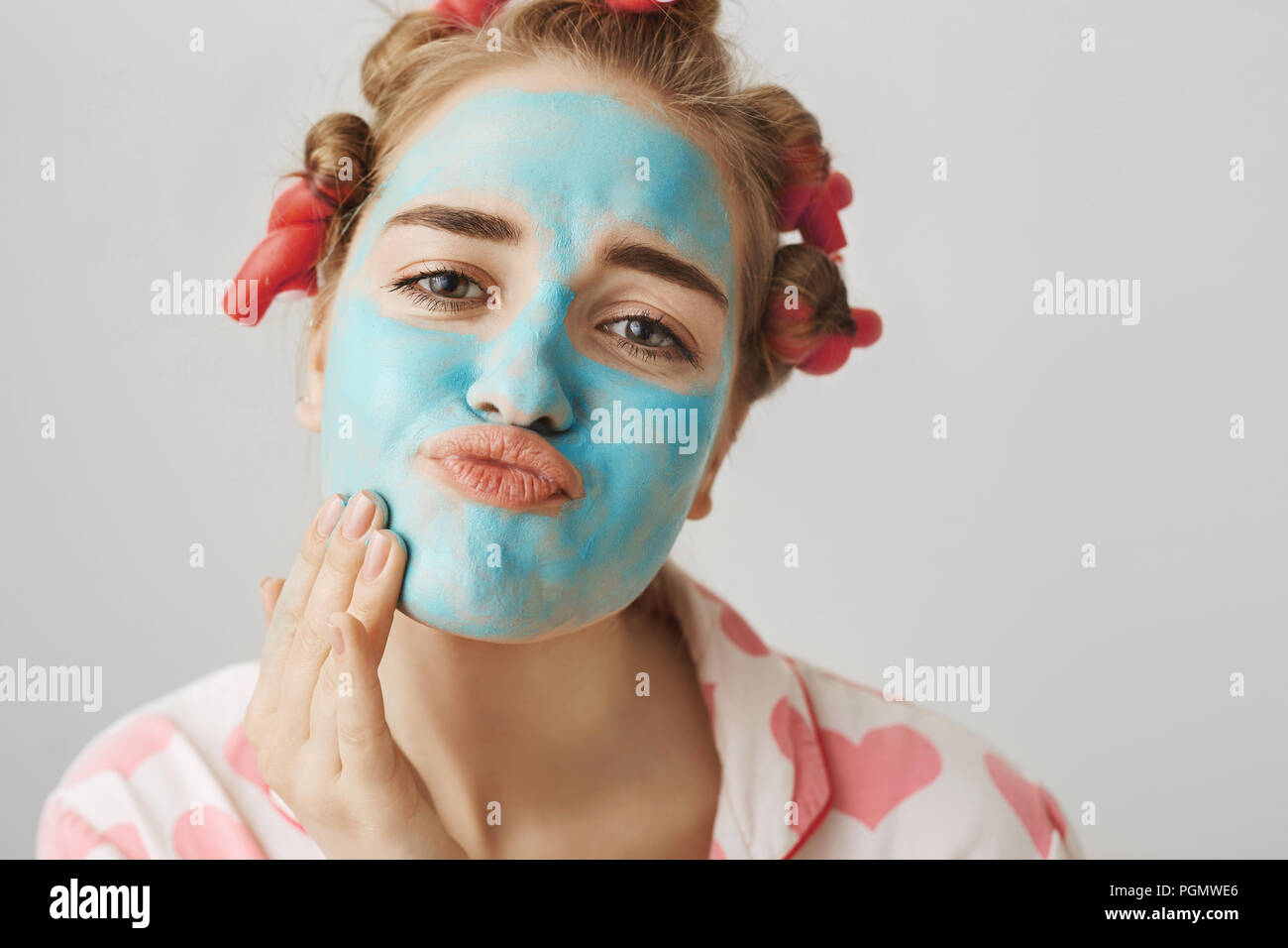 Close-up portrait of funny white woman with hair-curlers, wearing nightwear and folding lips while applying face mask with hand, looking at camera as if in mirror. Girl decided to take day off. - Stock Image