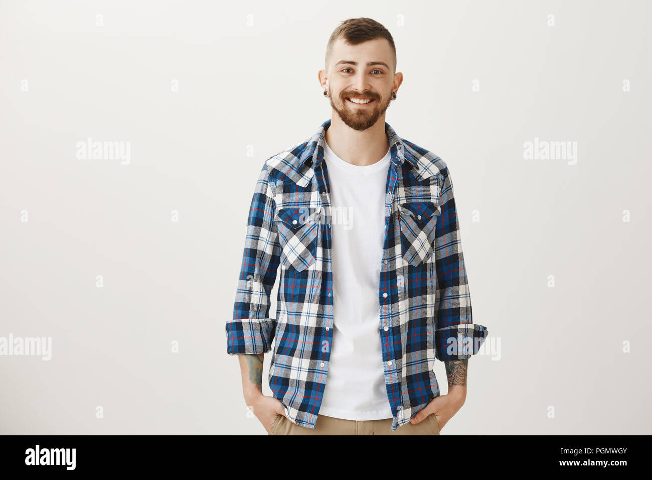 b685460fc9 Good-looing confident adult boyfriend with flesh-tunnels and beard standing  in blue plaid