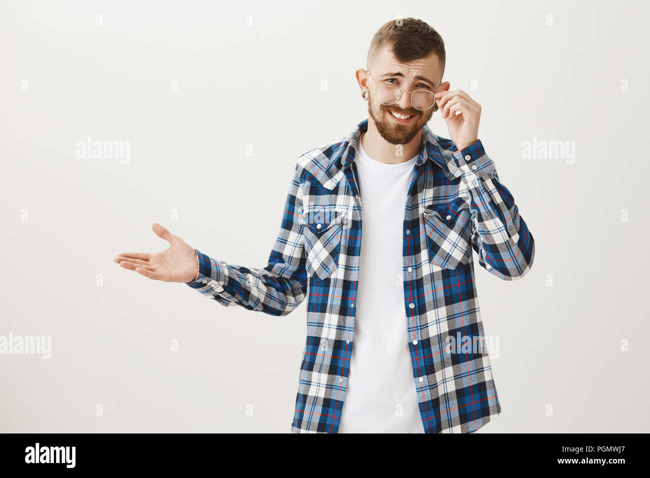 Who cares about rules. Portrait of attractive confident caucasian guy with beard in plaid shirt, taking off glasses and spreading palm cluelessly, hearing nonsense and expressing disbelief - Stock Image