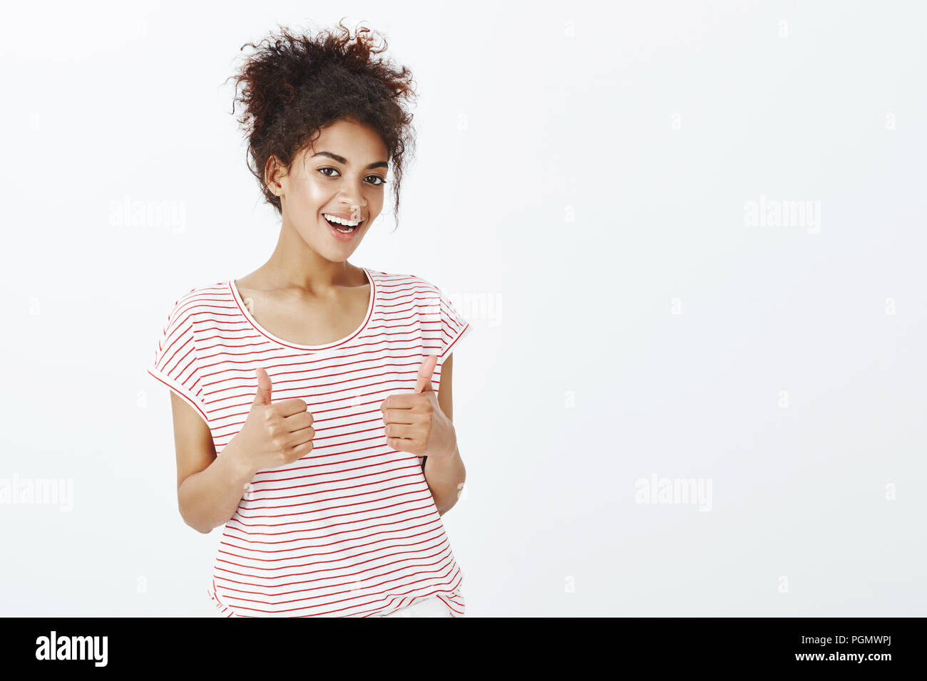 Totally agree with your opinion. Satisfied happy and outgoing woman with dark skin in striped t-shirt, raising thumbs up and smiling broadly, giving approval and liking interesting idea of friend Stock Photo