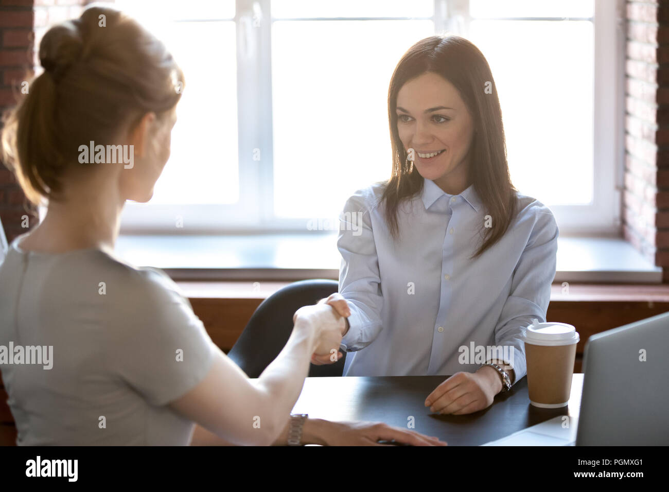 Female businesswomen shaking hands in office - Stock Image
