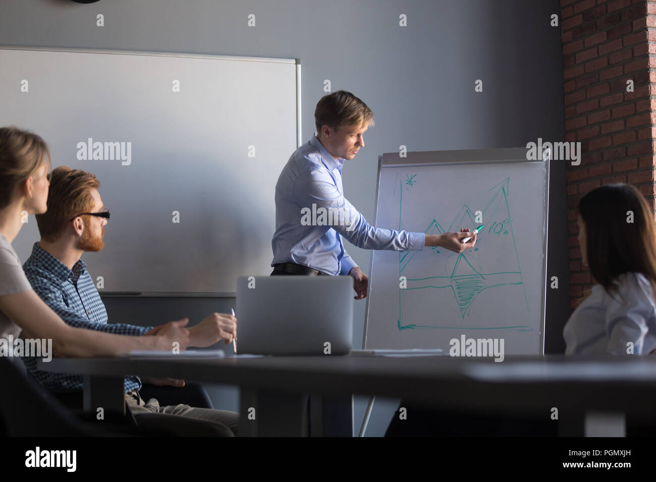 Male speaker giving flipchart presentation to colleagues - Stock Image