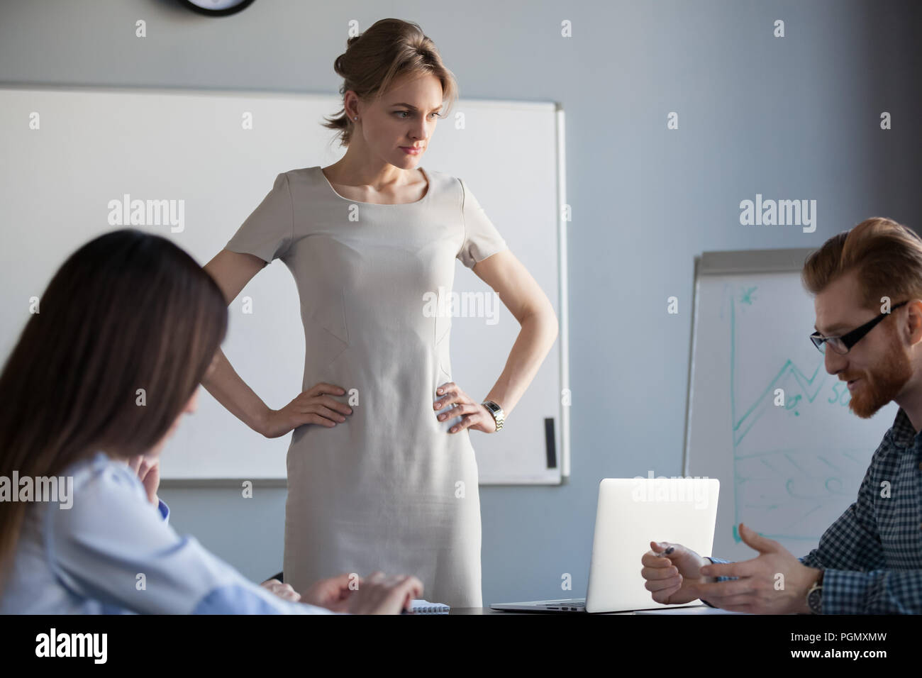 Angry businesswoman waiting for worker explanation of failure - Stock Image