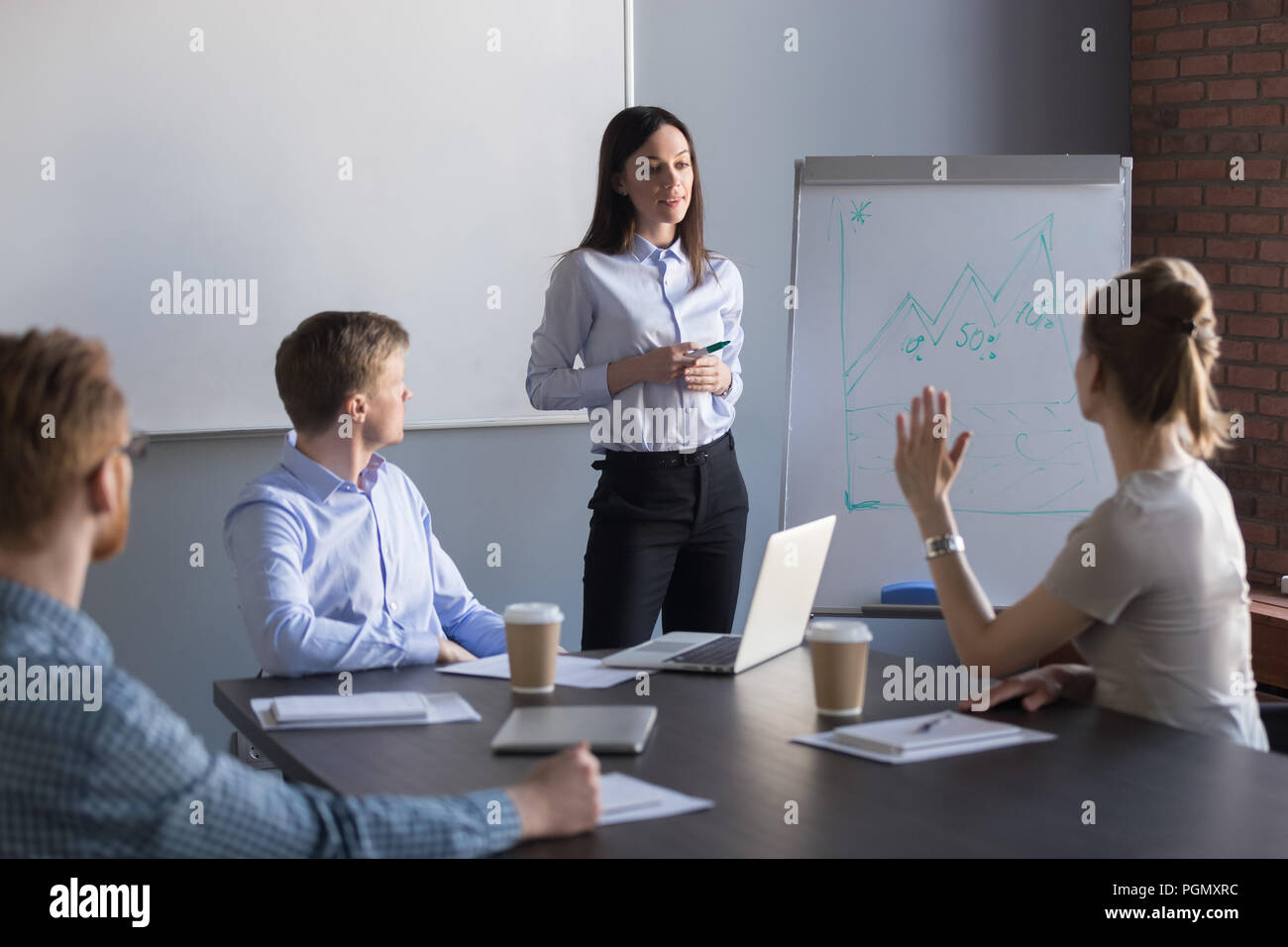 Female employee asking question to business speaker during metin - Stock Image