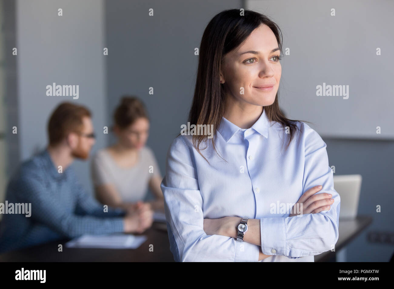 Smiling businesswoman looking from window dreaming of future suc Stock Photo