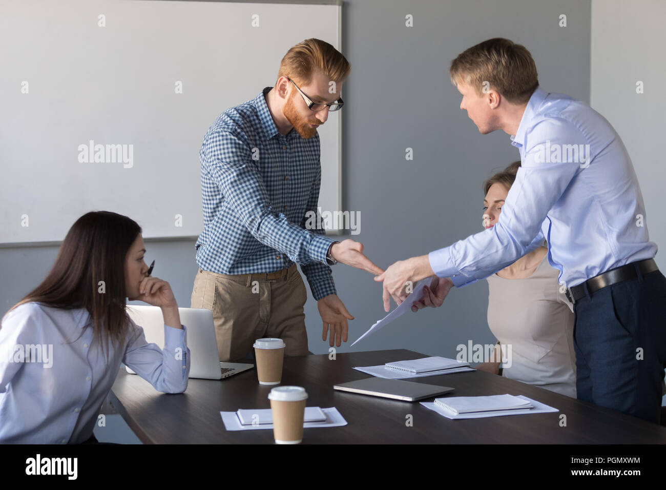 Angry coworkers disagree about contract terms and conditions - Stock Image