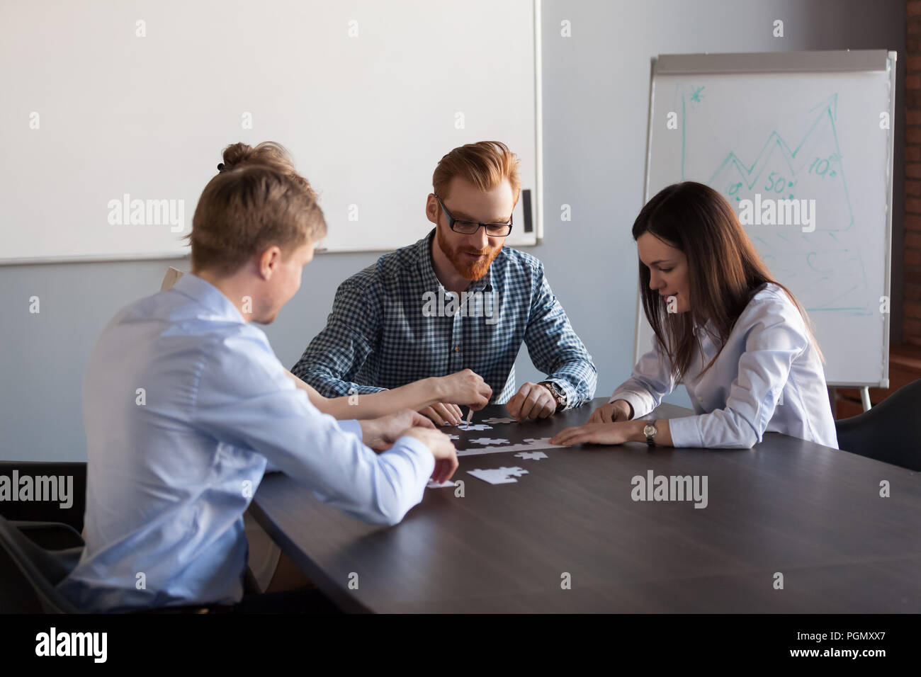 Employees assembling jigsaw puzzle during business meeting - Stock Image