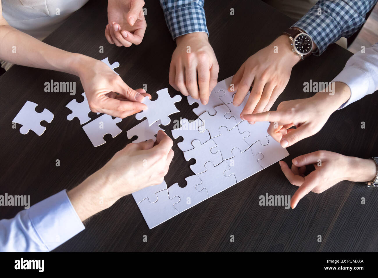 Close up of workers assembling jigsaw puzzle  - Stock Image