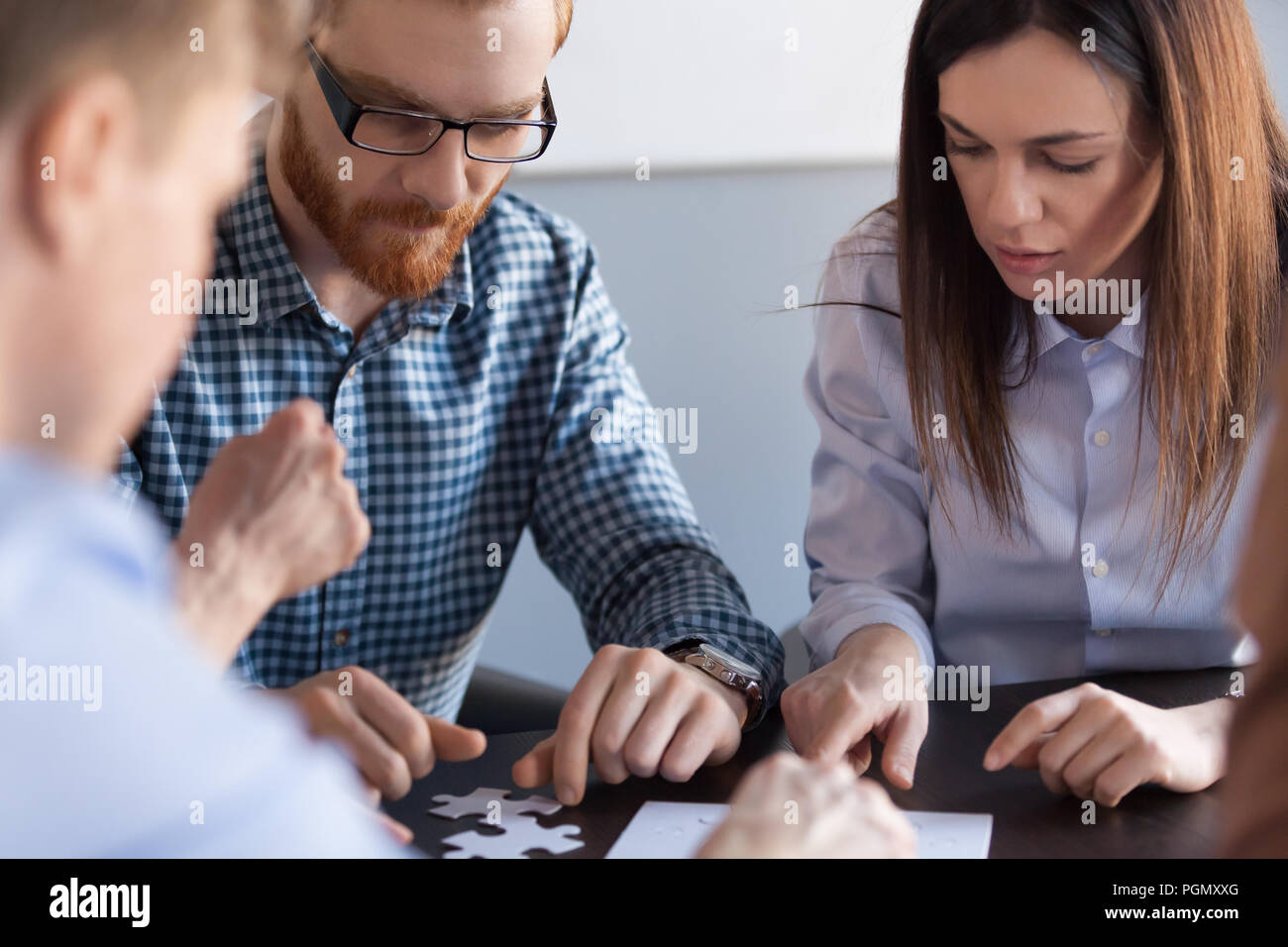Focused colleagues assembling jigsaw puzzle during meeting  - Stock Image