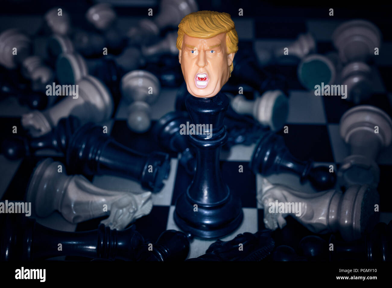 President Donald Trump standing on chessboard. Scattered chess pieces around. Stock Photo