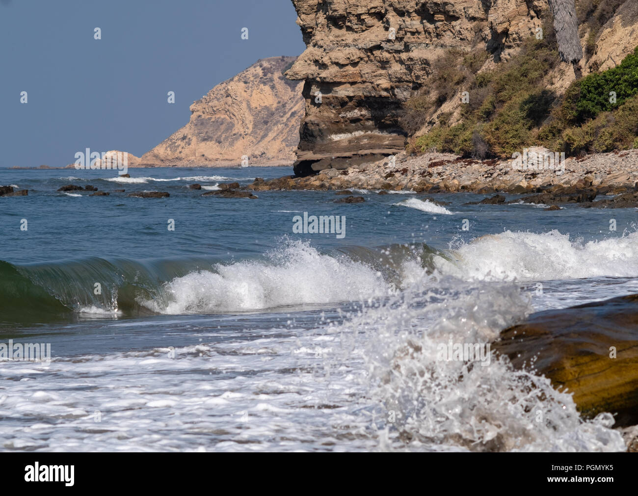 Gentle surf breaks in the morning sunshine on the Southern California coast. - Stock Image