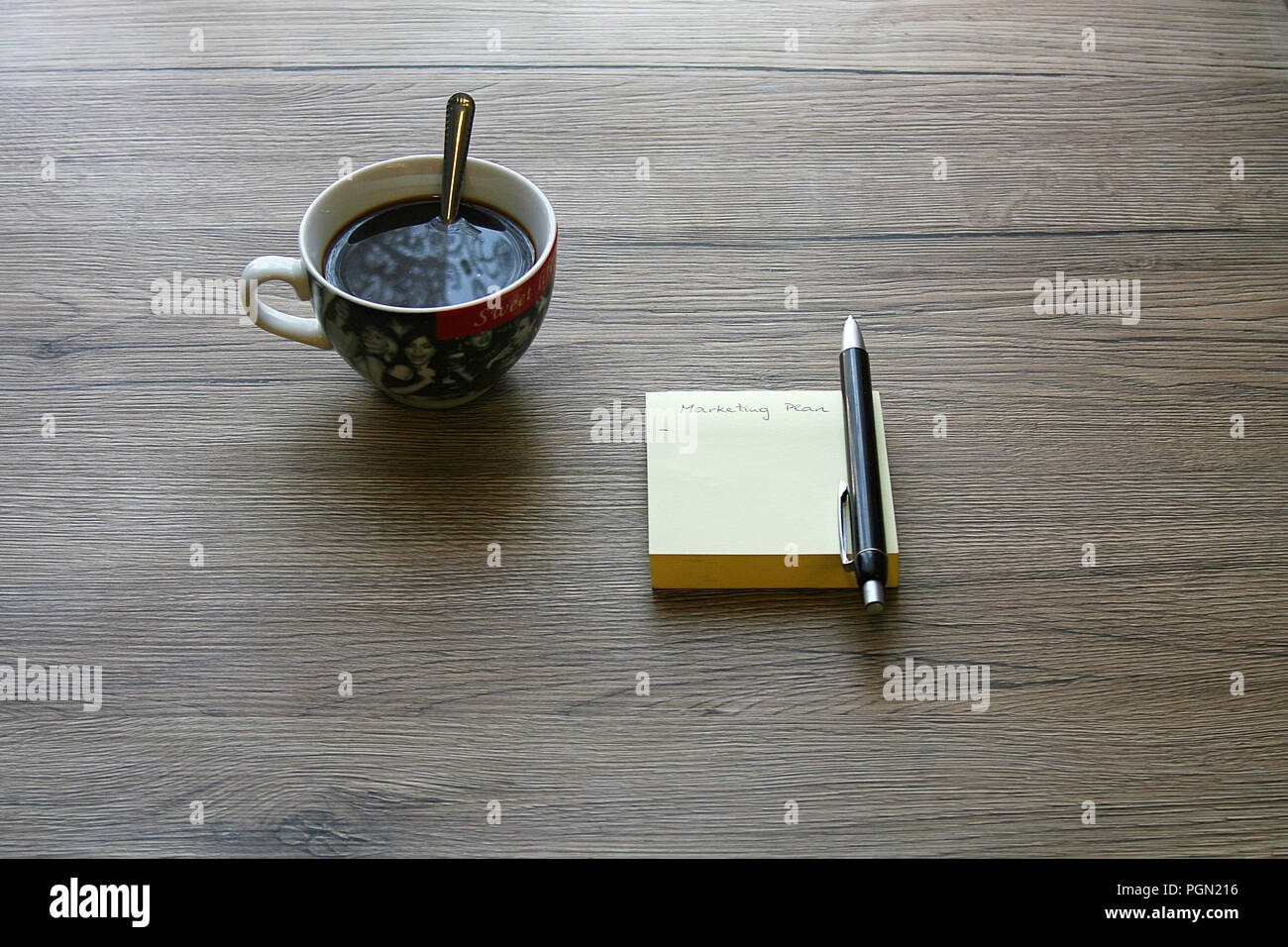 Wooden Office Desk Table With Marketing Plan Text On Notes, Pen And A Cup  Of Coffee