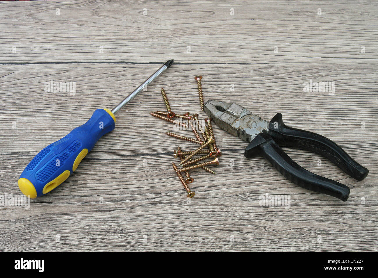 Screwdriver, Screws and Pliers Stock Photo