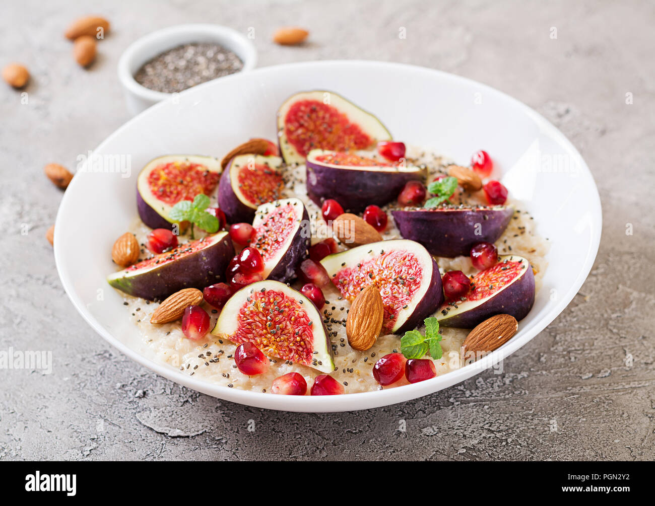 Delicious and healthy oatmeal with figs, almond and chia seeds. Healthy breakfast. Fitness food. Proper nutrition. - Stock Image