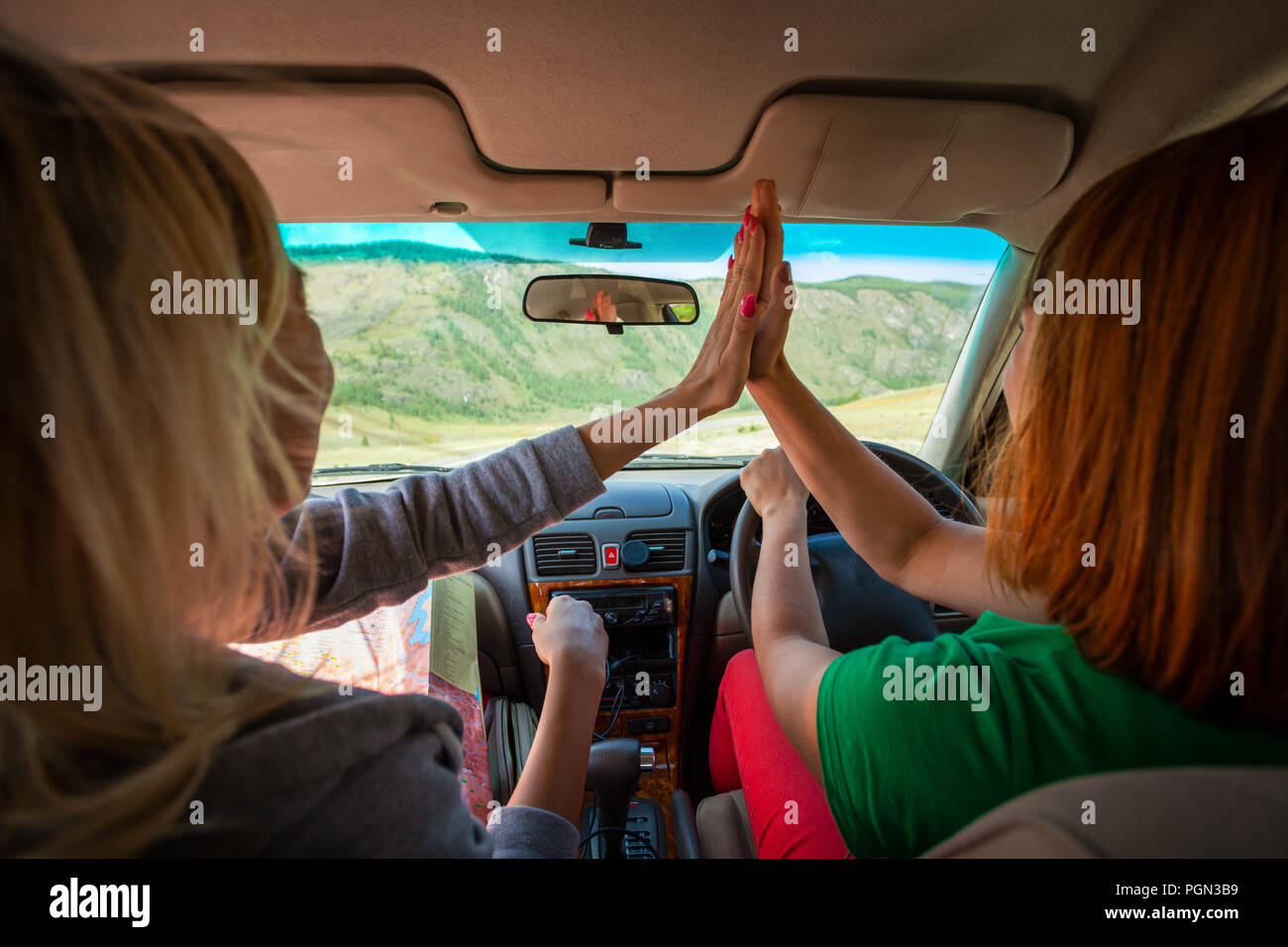 Guy and woman inside the car driving and eat pie  on the country roadway between fields with brown grass and snowy mountains . Sun is shining. Shoot f Stock Photo