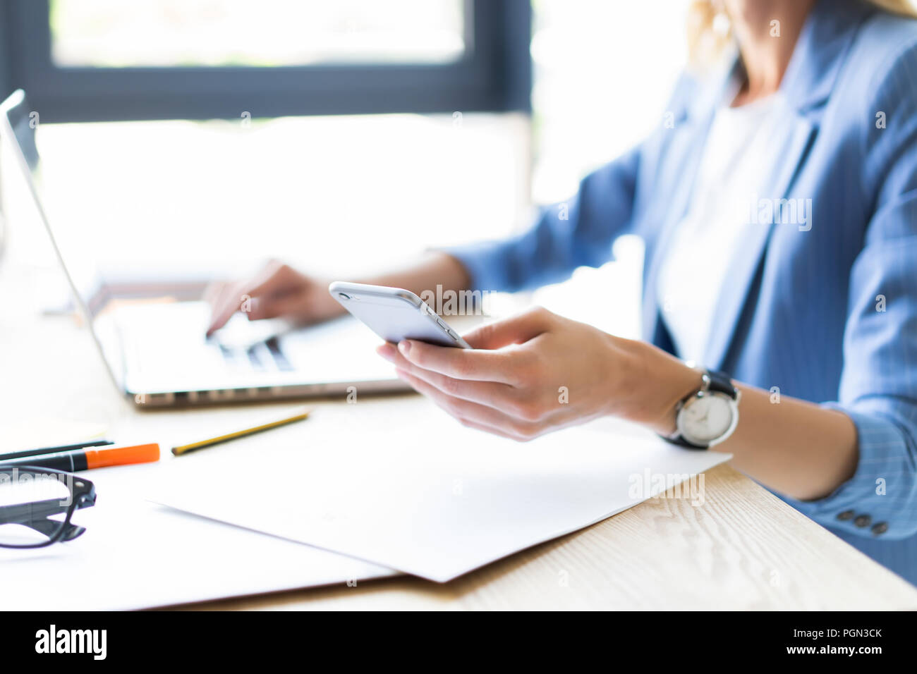 Businesswoman working at office desk and texting with her mobile phone. - Stock Image