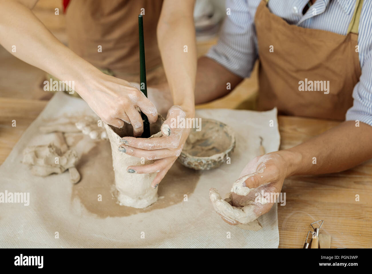 Female ceramist using working tool for forming vase - Stock Image