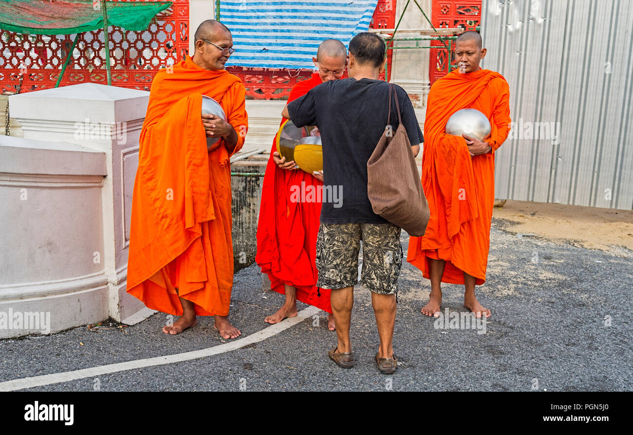 Buddhist Monk receiving alms and giving a blessing Bangkok Thailand South East Asia - Stock Image