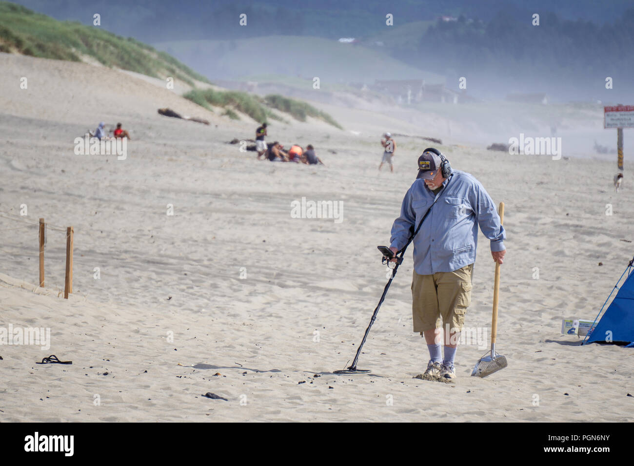 Old man treasure hunter or prospector using a metal detector seeking for lost objects Pacific City beach, Cape Kiwanda, Oregon coast, USA. - Stock Image