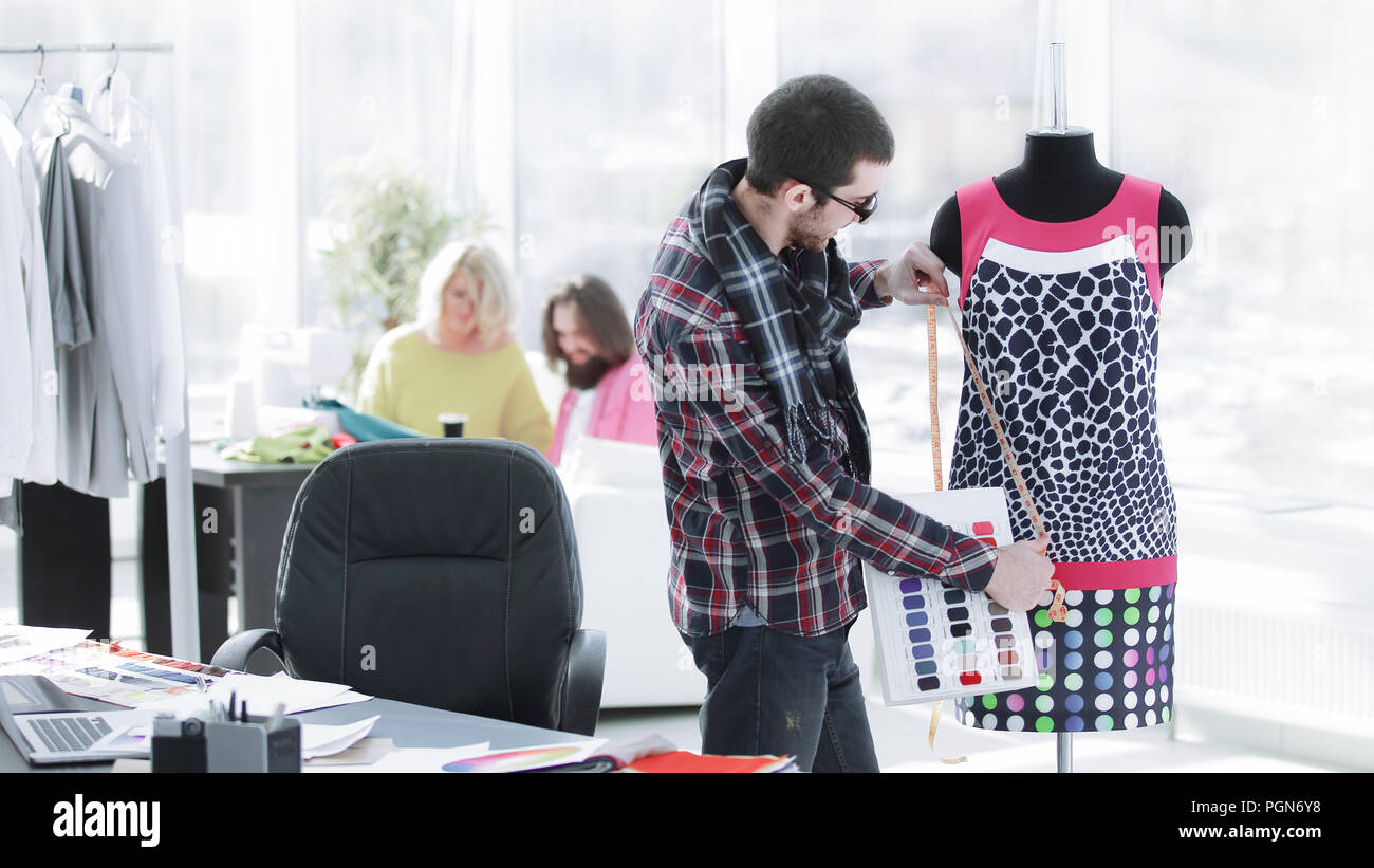 handsome fashion designer sitting with clothing sketches at the studio full of tailoring tools and clothes - Stock Image