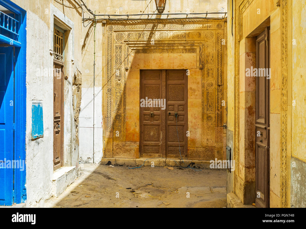 The frontage of the medieval mansion is decorated with fine carved pattern on stone wall and wooden door, Sfax, Tunisia. - Stock Image