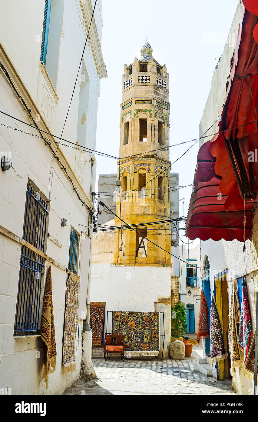 The outstanding octagonal minaret of the Ottoman Zaouia Zakkar mosque, surrounded by carpet stalls of local market, stretching along the maze of Medin - Stock Image