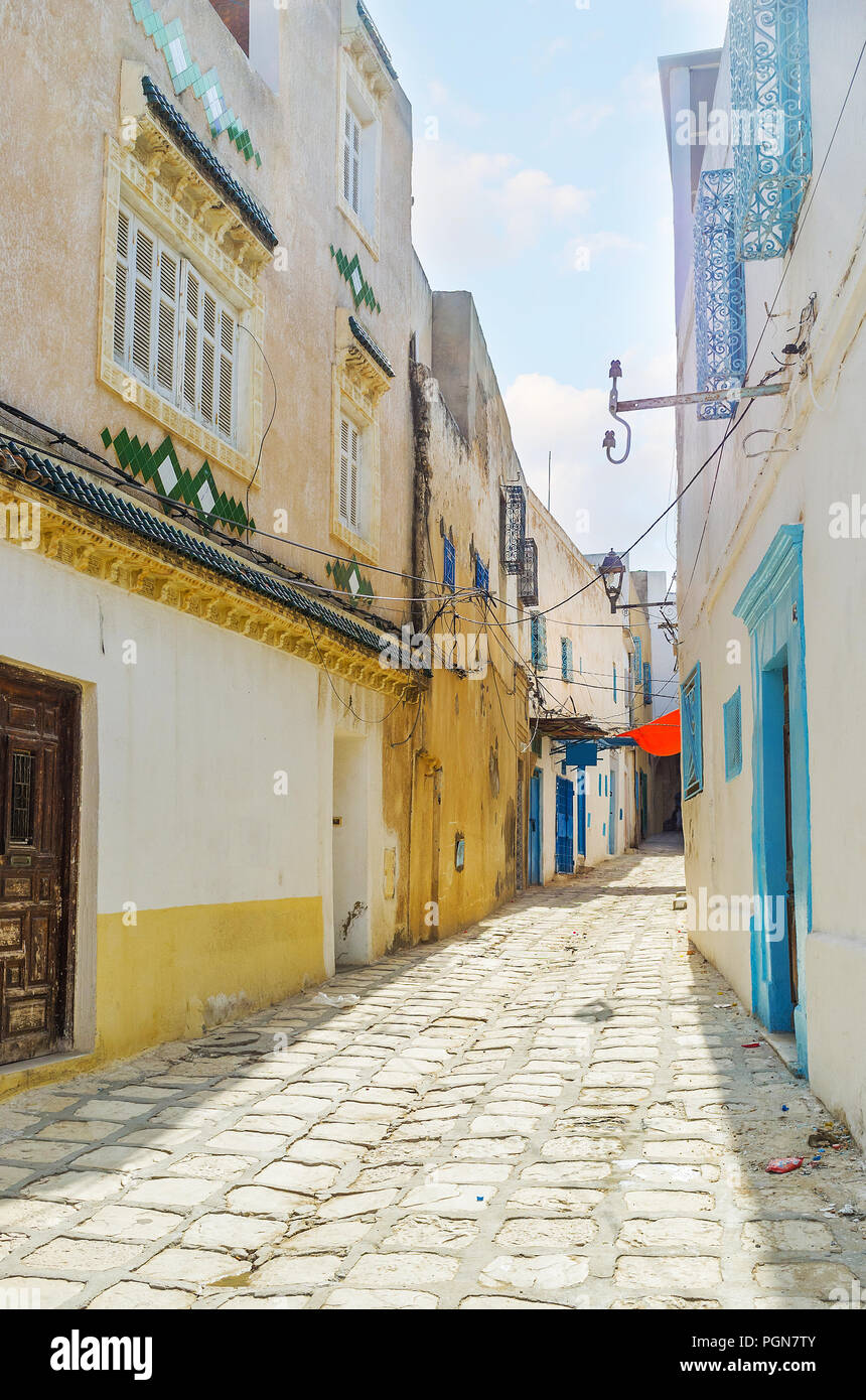 The narrow street of medieval Medina with row of authentic houses, decorated with bright blue ornamental grills on windows, tile patterns and colored  - Stock Image