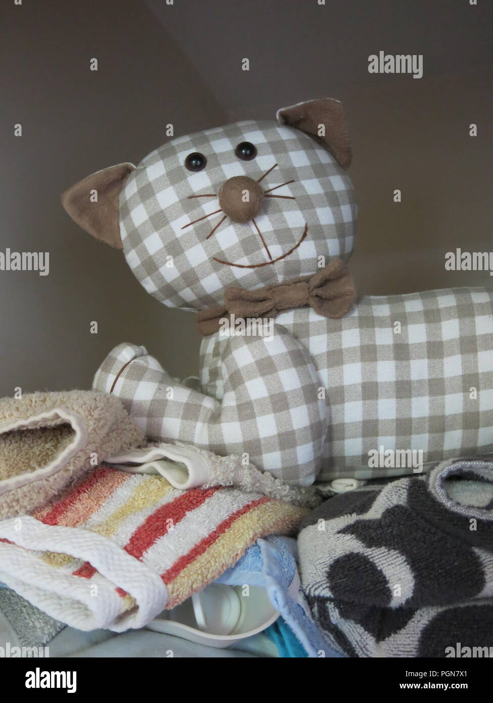 Cloth cat with a smiley face is hiding in the airing cupboard on top of a pile of towels - Stock Image